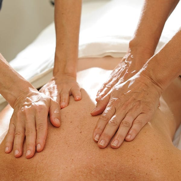 Person receiving therapeutic massage on a wellness retreat at the Amrit Yoga Institute
